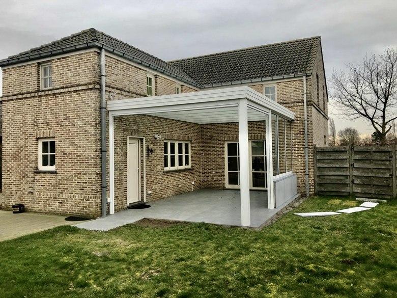 Aluminium terrasoverkapping met plat dak, geïntegreerde screens en een vast raam als wandafscherming