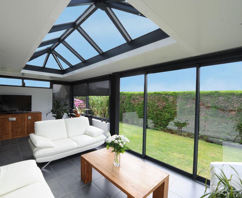 Een hedendaagse leefruimte met plat dak en lichtstraat - Vérandôme