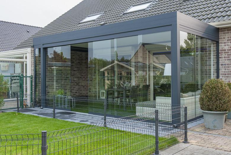 Een terrasoverkapping met lamellen dak en volledig afsluitbaar met glazen wandpanelen