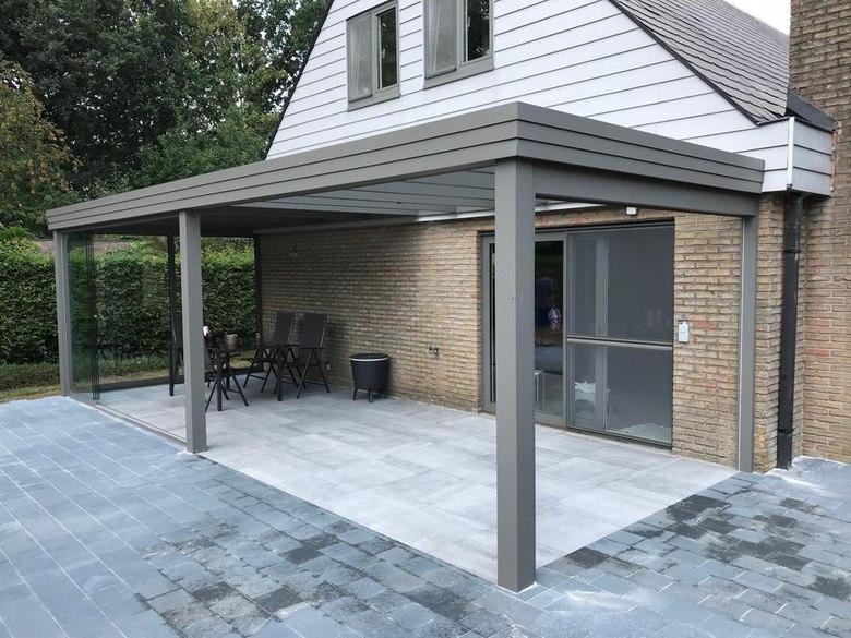 Een terrasoverkapping met plat dak waar glas en dakpanelen gecombineerd zijn